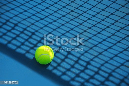 1153628111 istock photo Summer sport concept with tennis ball and net on hard tennis court. 1161263702