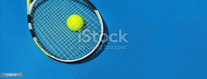 istock Summer sport concept with tennis ball and racket on blue hard tennis court. 1153628111
