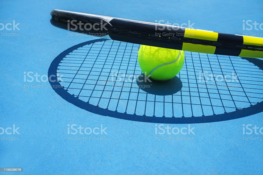 Summer sport concept with tennis ball and racket on blue hard tennis...