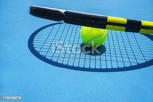 1153628111istockphoto Summer sport concept with tennis ball and racket on blue hard tennis court. 1155236276
