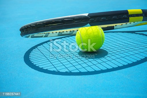 1153628111istockphoto Summer sport concept with tennis ball and racket on blue hard tennis court. 1155237441