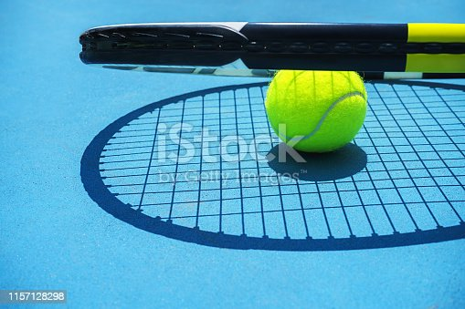 1153628111 istock photo Summer sport concept with tennis ball and racket on blue hard tennis court. 1157128298