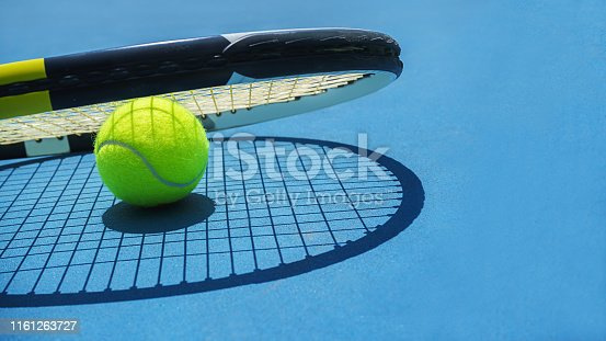 1153628111 istock photo Summer sport concept with tennis ball and racket on blue hard tennis court. 1161263727