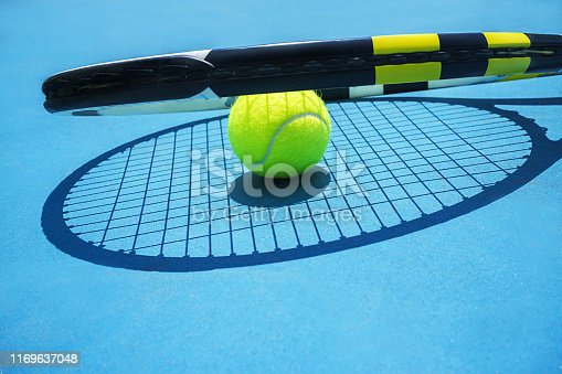 1153628111istockphoto Summer sport concept with tennis ball and racket on blue hard tennis court. 1169637048