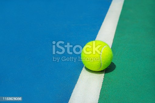 1153628111istockphoto Summer sport concept with tennis ball on white line on hard tennis court. 1153628056