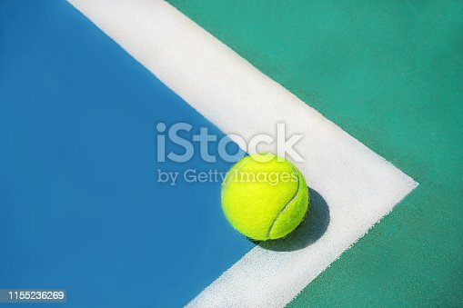 1153628111 istock photo Summer sport concept with tennis ball on white line on hard tennis court. 1155236269