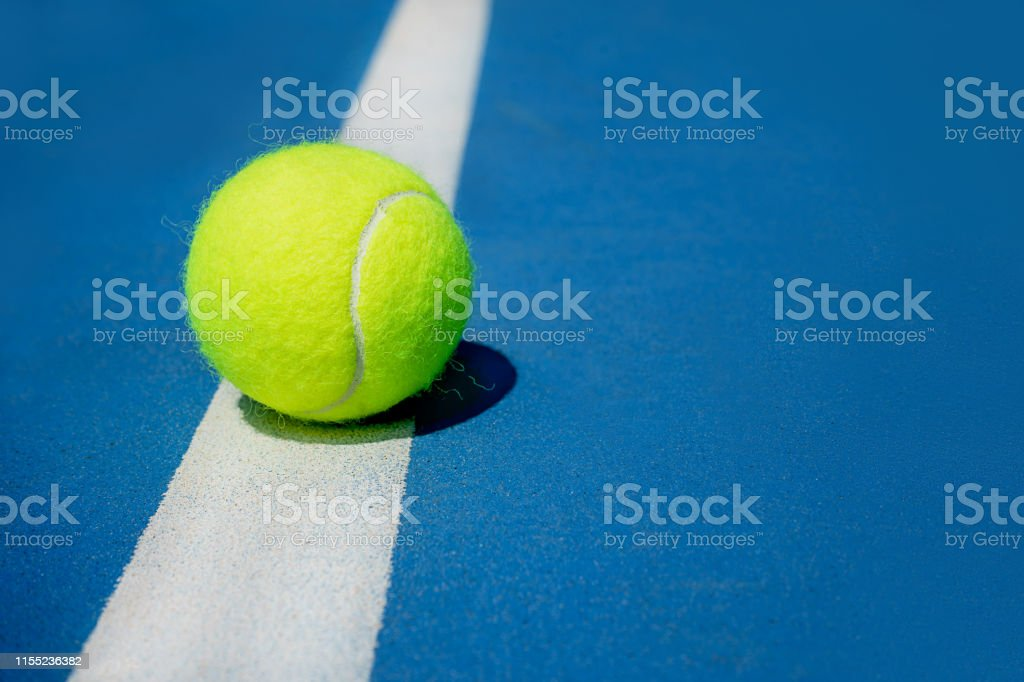 Summer sport concept with tennis ball on white line on hard tennis...