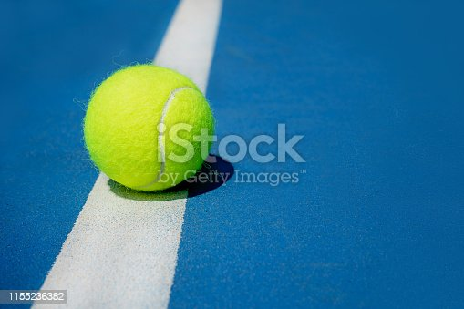 1153628111 istock photo Summer sport concept with tennis ball on white line on hard tennis court. 1155236382