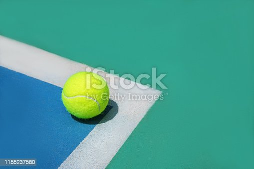 1153628111istockphoto Summer sport concept with tennis ball on white line on hard tennis court. 1155237580