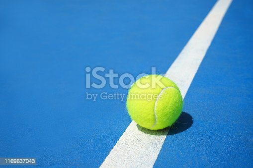 1153628111 istock photo Summer sport concept with tennis ball on white line on hard tennis court blue color. 1169637043