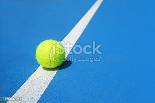 1153628111 istock photo Summer sport concept with tennis ball on white line on hard tennis court blue color. 1169637044