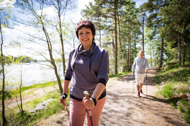 Summer sport in Finland - nordic walking Summer sport in Finland - nordic walking. Man and mature woman hiking in green sunny forest. Active people outdoors. Scenic peaceful Finnish summer landscape. nordic walking stock pictures, royalty-free photos & images