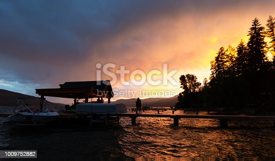 Silhouette of people looking at sunset while waves roll in under pier