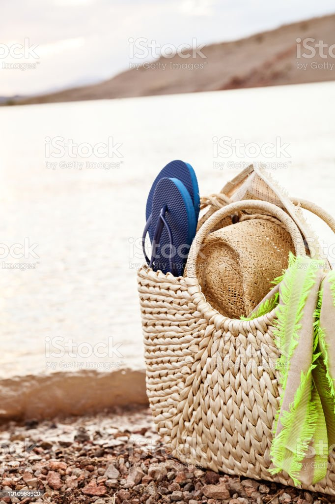 Summer Straw Bag And Beach Accessories On The Shore stock photo