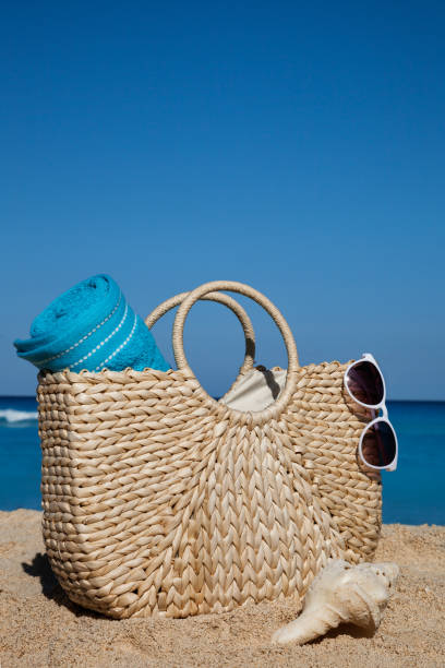Summer straw bag with blue towel and sunglasses on a tropical sandy beach stock photo