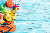 high angle view of some summer stuff, such a pair of orange flip-flops, an inflatable donut and an inflatable pineapple, or a beach pail, on a blue rustic wooden table with some blank space