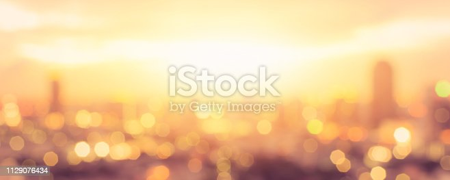 istock Summer sun blur golden hour sky sunset with city rooftop view  background cityscape office building landscape blurry urban lights skyline bokeh for evening party 1129076434