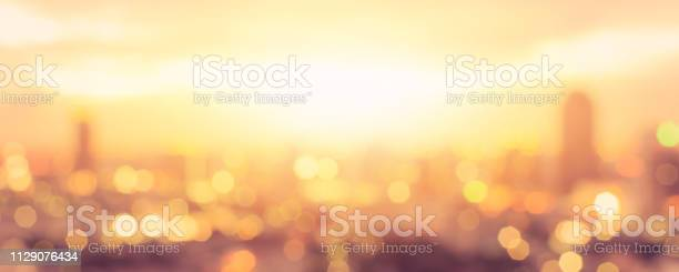Photo of Summer sun blur golden hour sky sunset with city rooftop view  background cityscape office building landscape blurry urban lights skyline bokeh for evening party