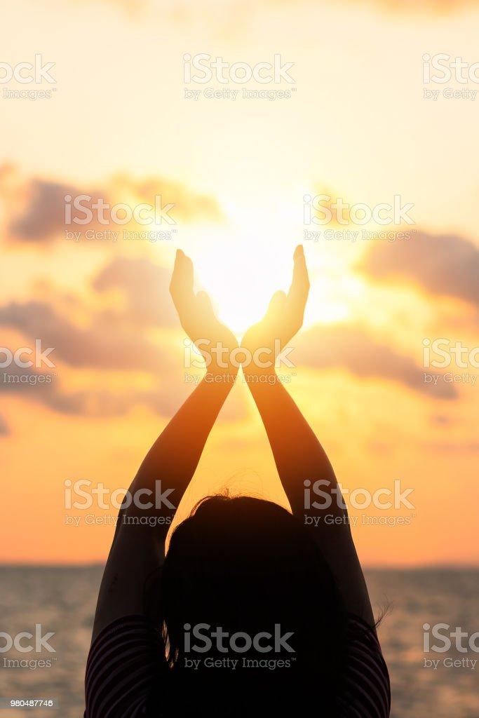 Yaz güneşi Haziran gündönümü kavramı ve rahatlatıcı, meditasyon ve doğal okyanus ya da deniz arka plan ile sahilde sıcak altın saat gökyüzü günbatımı tutan mutlu genç kadının elleri silüeti stok fotoğrafı