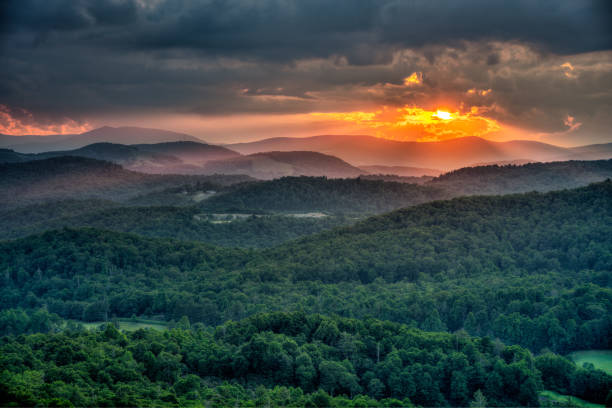 Summer Sun setting on the Blue Ridge Mountains in North Carolina Flat Rock overlook, just a 10 minute hike from the Blue Ridge Parkway.  Popular spot with locals to view a sunset. appalachia stock pictures, royalty-free photos & images