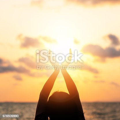 Summer sun solstice concept and silhouette of happy young woman's hands relaxing, meditating and holding sunset against warm golden hour sky on the beach with ocean or sea background