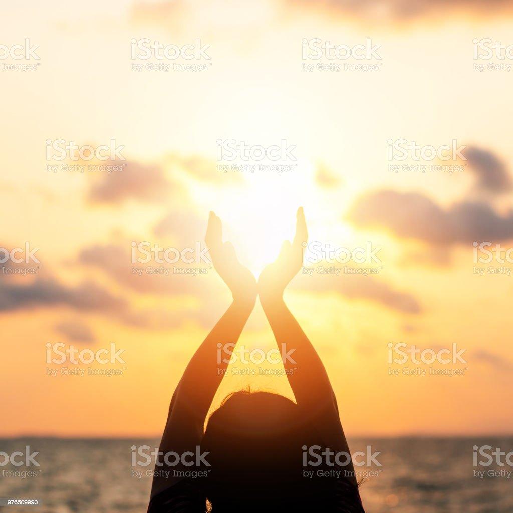 Yaz güneş gündönümü kavramı ve rahatlatıcı, meditasyon ve okyanus ya da deniz arka plan ile sahilde sıcak altın saat gökyüzü günbatımı tutan mutlu genç kadının elleri silüeti stok fotoğrafı
