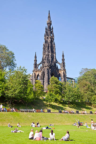Summer Sunday: East Princes Street Gardens, Edinburgh Edinburgh, Scotland, UK - 3rd July, 2011: Groups of mostly young adults and families sunbathing, relaxing and chatting in East Princes Street Gardens in central Edinburgh, Scotland, on a hot summer Sunday. The neo-gothic Scott Monument is centre,  above the trees slightly right of centre. Princes Street Gardens were formed in 1820, after the draining of the Nor Loch. princes street edinburgh stock pictures, royalty-free photos & images