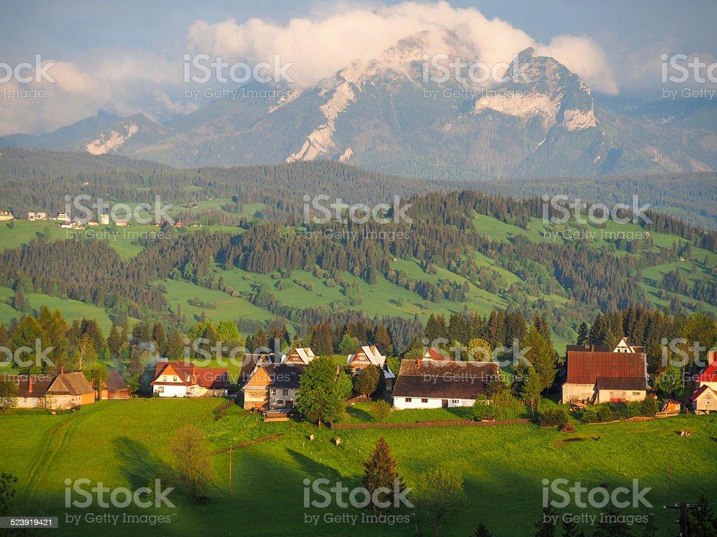 Summer sunrise mountain village outskirts view and Tatra range b stock photo