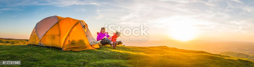 930810564 istock photo Summer sunset camping young hikers beside mountain top tent panorama 612731592