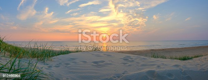 View from the dunes on the sand beach of the North Sea shore on the coast line in The Netherlands during a beautiful summer sunset after a warm day in August.