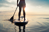 summer sunset SUP rear view part of woman paddling with stand up paddle board alone in lake