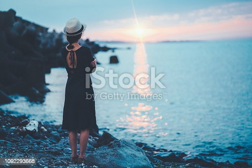 Young woman at the beach staring the sunset