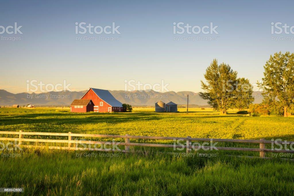 Atardecer de verano con un granero rojo en la Montana rural y montañas rocosas - foto de stock