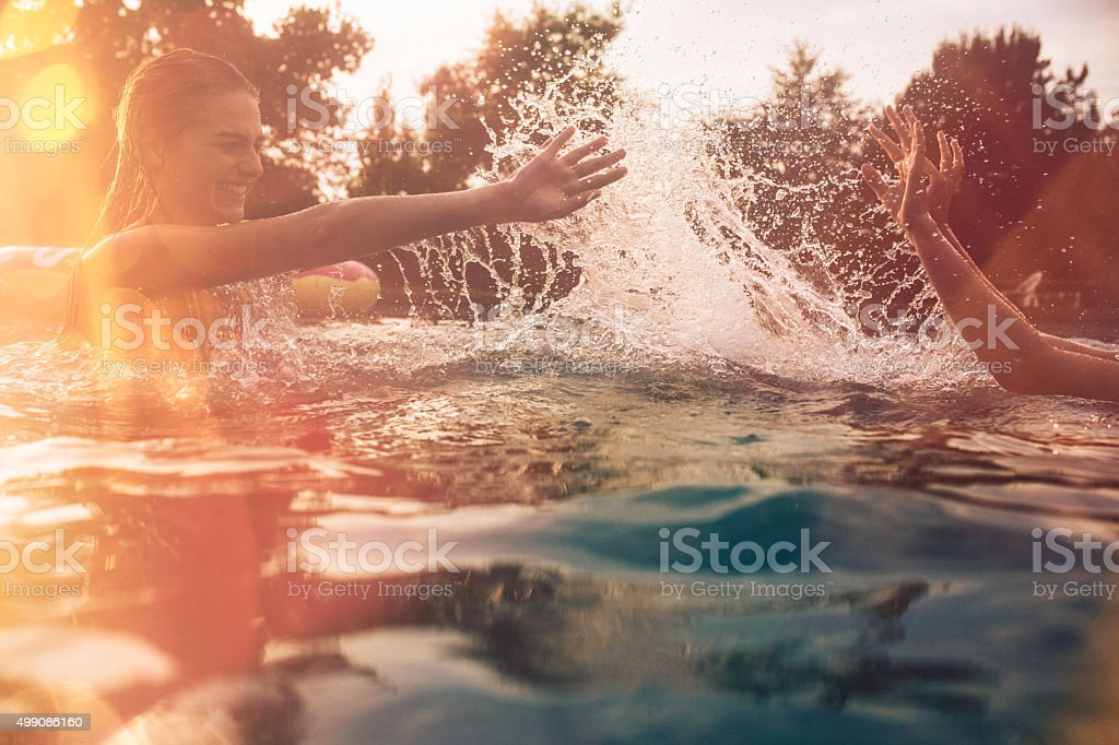 Summer swimming pool with girls splashing water playfully stock photo