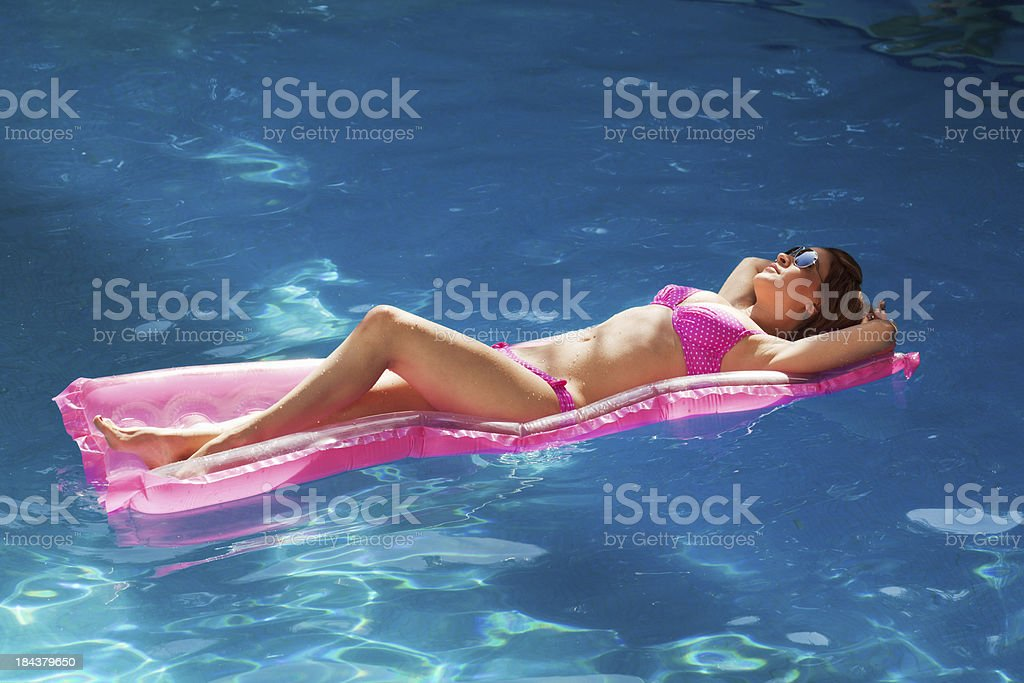Summer Swimming Pool- Young Woman Relaxing on Mattress royalty-free stock photo