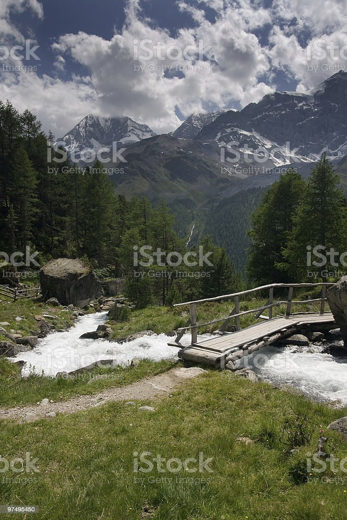 Summer swiss alps with creek and bridge royalty-free stock photo