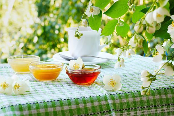 summer tea with honey under the jasmine bush. - kastanienhonig stock-fotos und bilder
