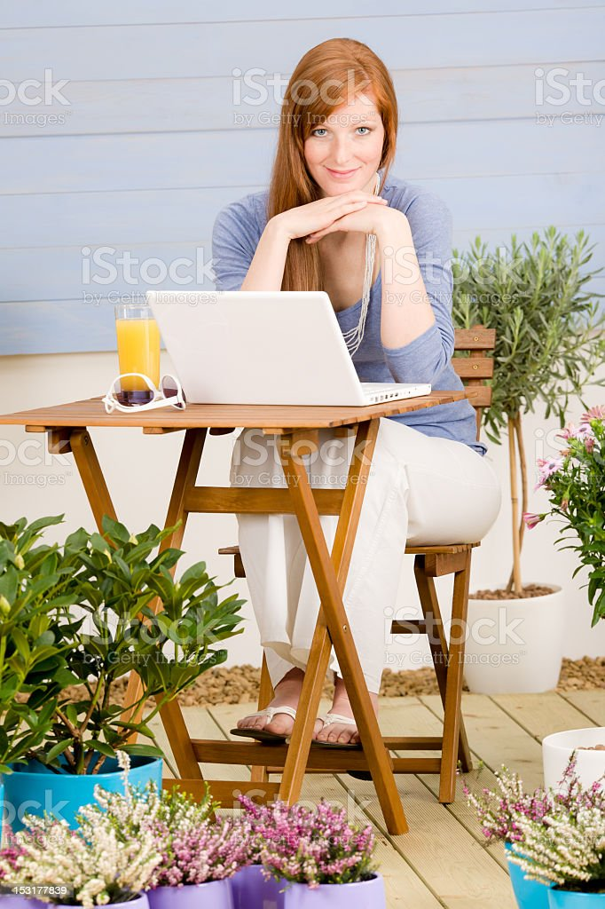 Summer terrace redhead woman with laptop royalty-free stock photo
