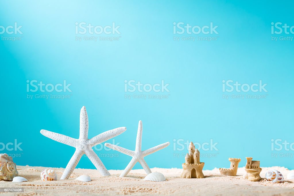 Summer theme with starfish and sand castle stock photo