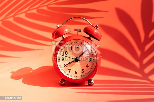 istock Summer time concepts idea with alarm clock and tropical leaf shadow on colorful background.holiday decoration 1130945055
