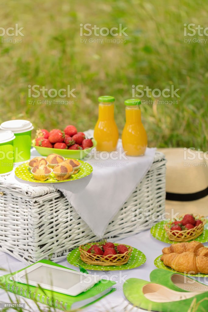 Summer time: picnic on the grass - coffee and croissants, juice and berries. stock photo