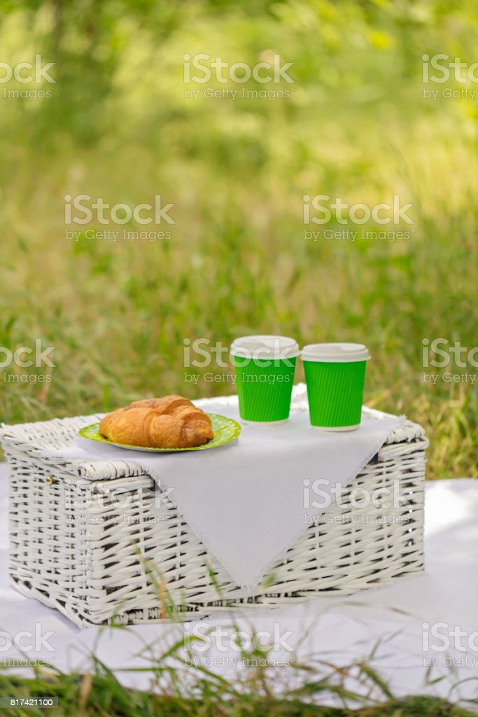 Summer time: picnic on the grass - coffee and croissants. stock photo
