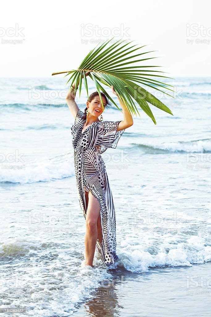 Summer time Summer portrait of beautiful woman wearing summer dress and standing in the ocean with palm leaf over her head. 25-29 Years Stock Photo