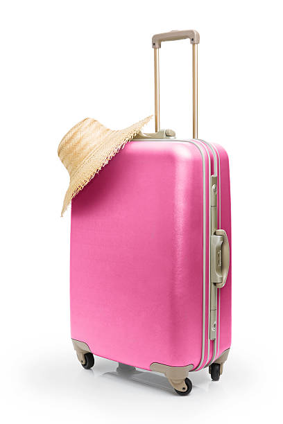 Summer time travel with pink suitcase and straw hat  stock photo
