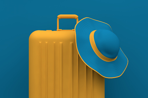 Summer Travel concept, hat and suitcase on blue background