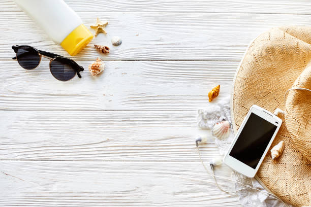 summer travel vacation concept, flat lay, space for text. phone with empty screen and sunglasses and sunscreen shells hat on white wooden background top view. hello summer. wanderlust - phone, travelling, copy space imagens e fotografias de stock