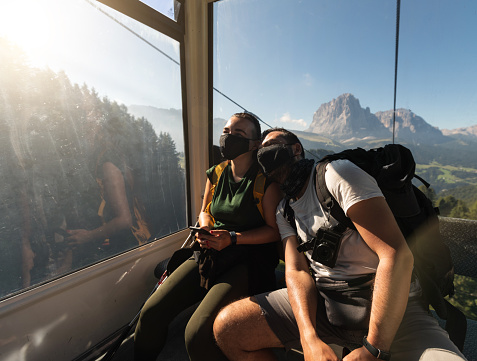 Summer travelers wearing face masks against Covid virus in a cableway on the Dolomites