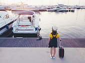 Rear view of passenger with suitcase at the marina ready for boarding