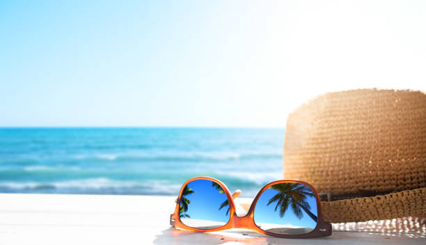 summer tropical beach background; glasses and palm tree reflex - holiday foto e immagini stock