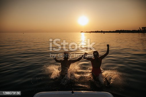 Happy young couple holding hands and jumping into the sea from a pedal boat at beautiful sunset. Active and amusing summer vacation